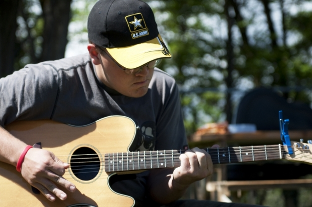 Adam Howerton plays the guitar at a farewell party